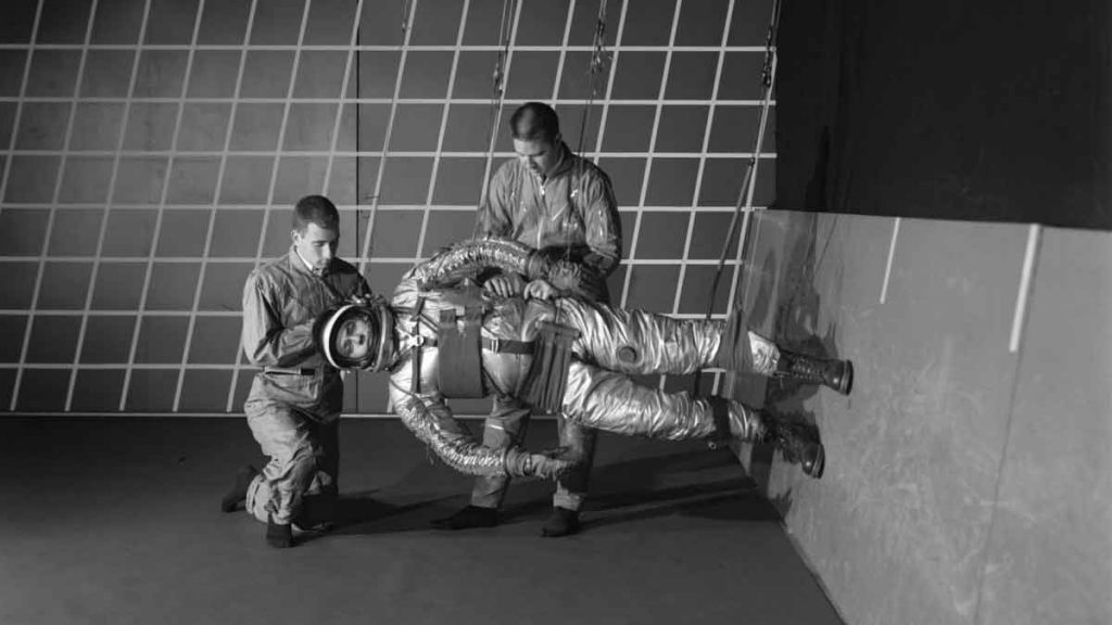 A test subject being suited up for studies on the Reduced Gravity Walking Simulator at Langley Research Center, 1963