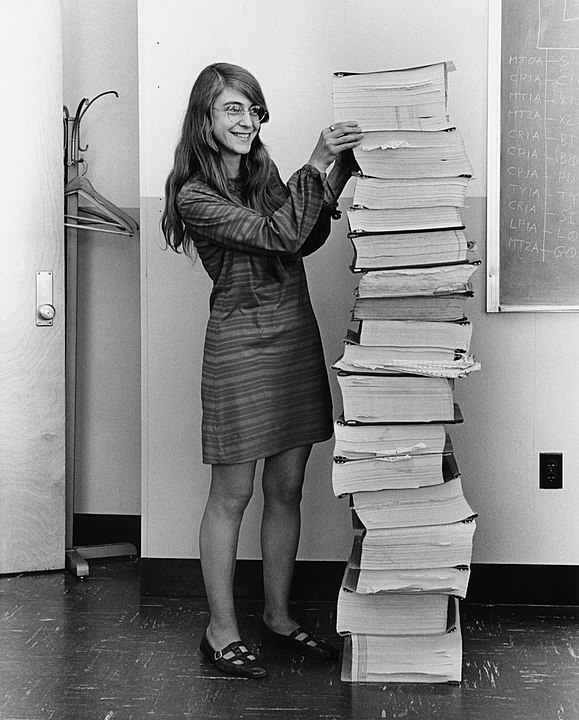 Hamilton in 1969, standing next to listings of the software she and her MIT team produced for the Apollo project. Photo credits: Wikimedia Commons