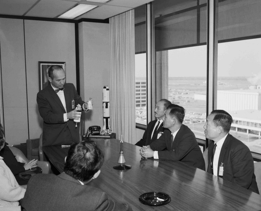 Maxime Faget explains a model of the Apollo Spacecraft to members of the Korean National Assembly. Credit: NASA