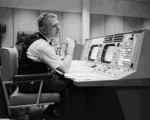 S65-22203 (April 1965) -- Prior to the Gemini-Titan 4 mission, flight director Eugene F. Kranz is pictured during a simulation at the Flight Director console in Houston's Mission Control Center on the Manned Spacecraft Center site. GT-4 was the first mission to be at least partially controlled from the Houston site. Photo credit: NASA